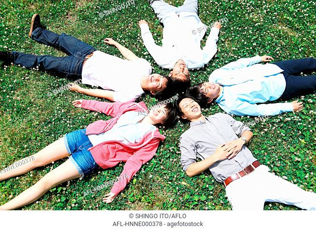 Group of young Japanese friends laying on grass