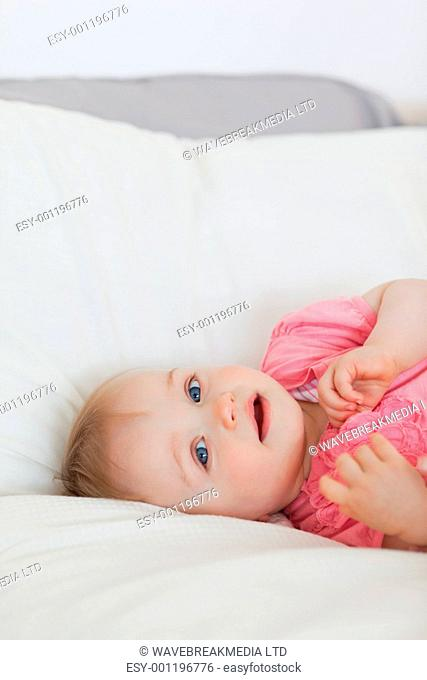 Lovely blond baby lying on a bed in an appartment