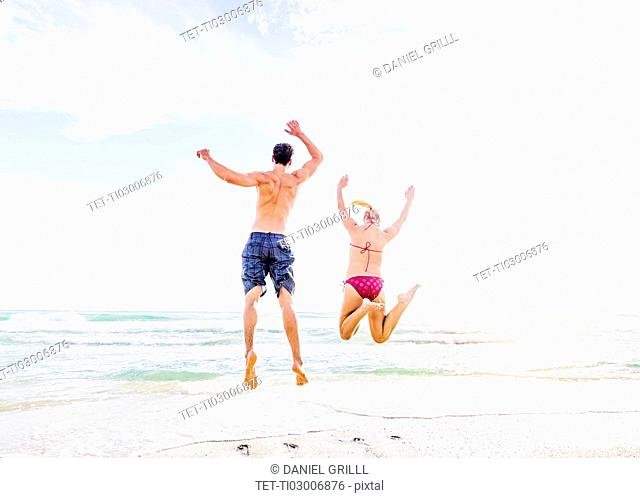 Rear view of young couple jumping on beach