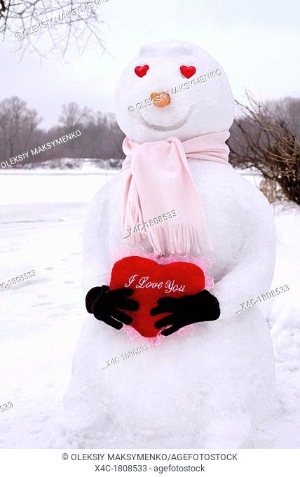 Smiling snowman with heart-shaped eyes holding a red heart with I Love You written on it in his hands  Winter holidays, Valentine's Day romantic concept