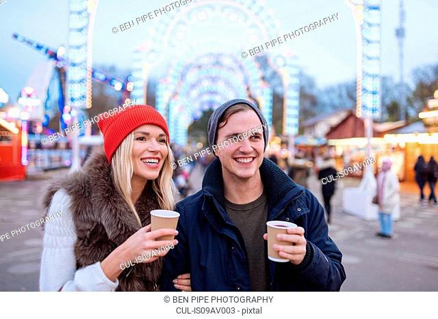 Happy young couple drinking mulled wine at Xmas festival, Hyde Park, London, UK