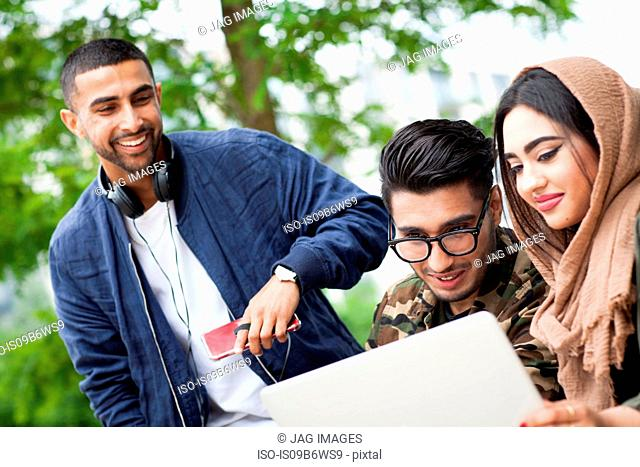 Three friends outdoors, looking at laptop