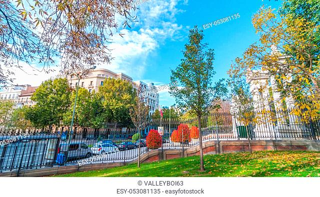 Cars parked on the side of Alfonso XII Street in Madrid, Spain, as seen from inside the fence in Retiro Park. Unusually warm November day in one of the main...