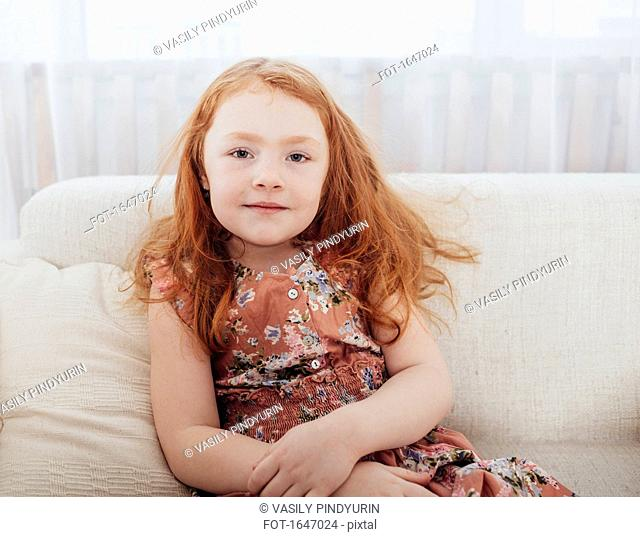 Portrait of smiling girl with redhead sitting on sofa at home