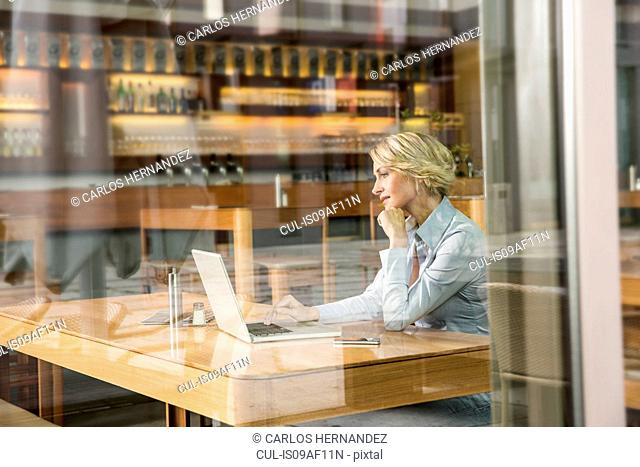 Businesswoman using laptop, view through window