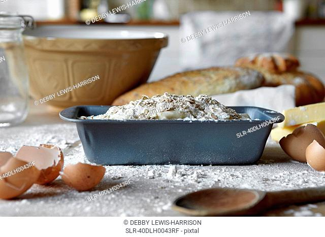 Bread loaves and dough in messy kitchen