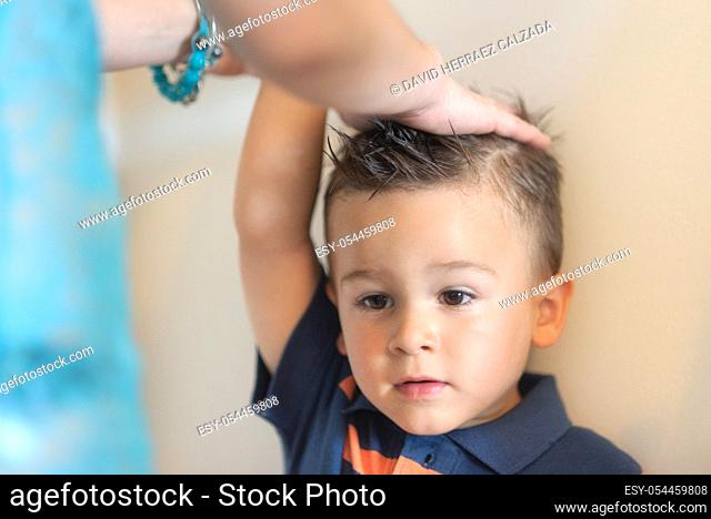Mother measuring height of her son near white wall