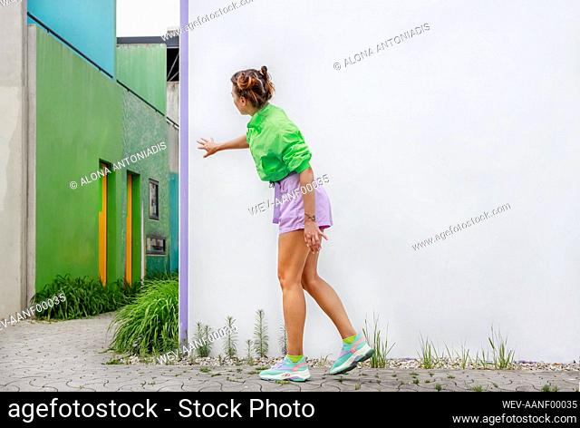 Young woman standing on footpath in front of white wall