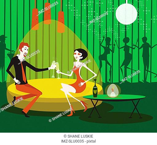 A couple clinking champagne in a private lounge at a club