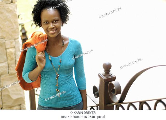 Young African woman with jacket over shoulder smiling