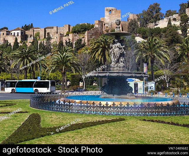 Fountain (El fuente de tres gracias) on the roundabout entering paseo Parque with the Alcazaba in the background - Malaga, Spain
