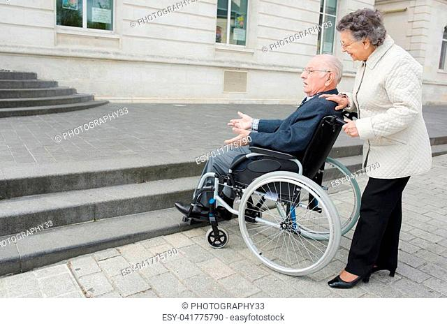 old man on wheelchair and woman carrying him