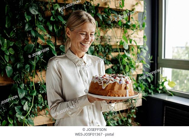 Smiling businesswoman holding birthday cake in green office