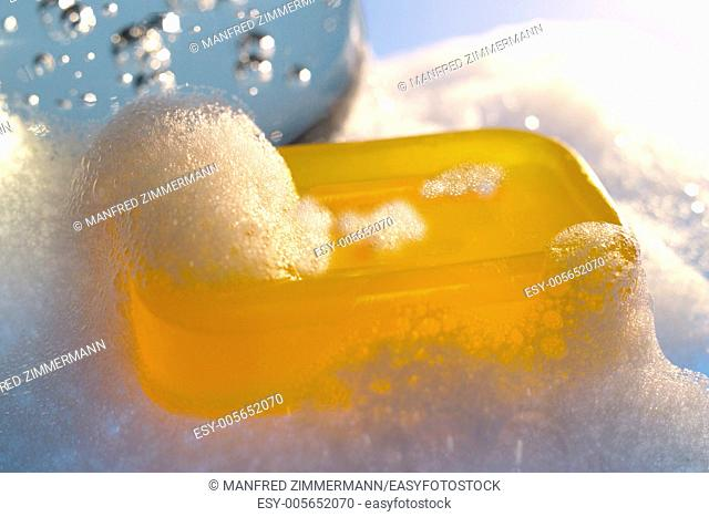 Piece of yellow glycerine soap is in the midst of foam