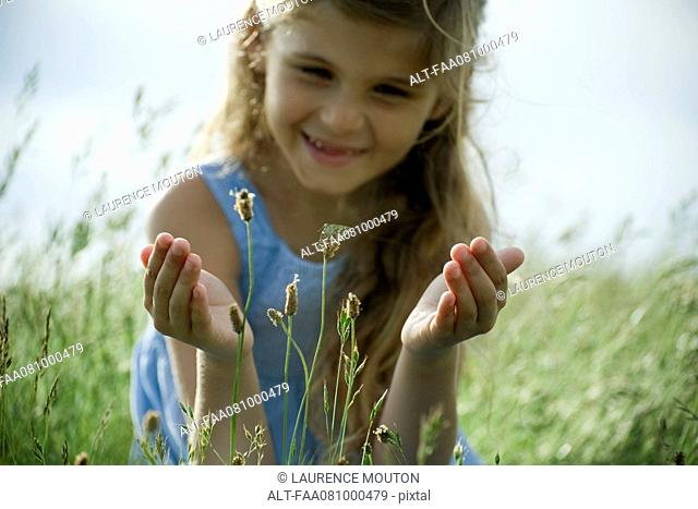 Girl staring at butterfly on wildflower