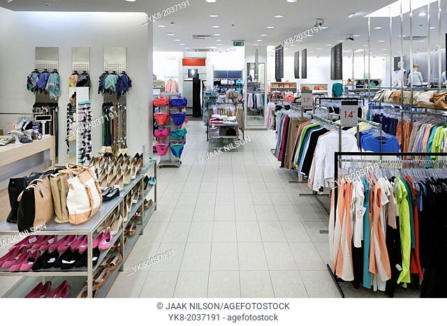 Fashion shop interior with display. Clothing and bags in retail store. Large aisle and elevated view