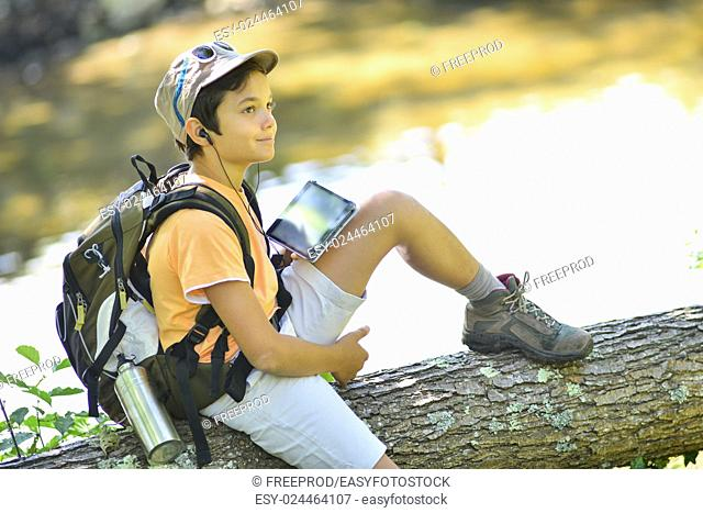Young boy seeking his path on a tablet during a hike