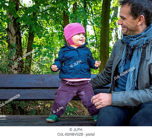 Father and baby girl on park bench by forest