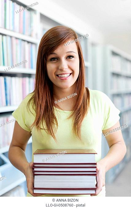 Beautiful student holding a books in library Debica, Poland