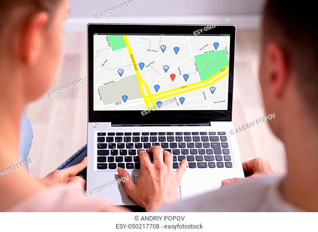 Rear View Of Couple Using GPS Map With Navigation Pointer On Laptop