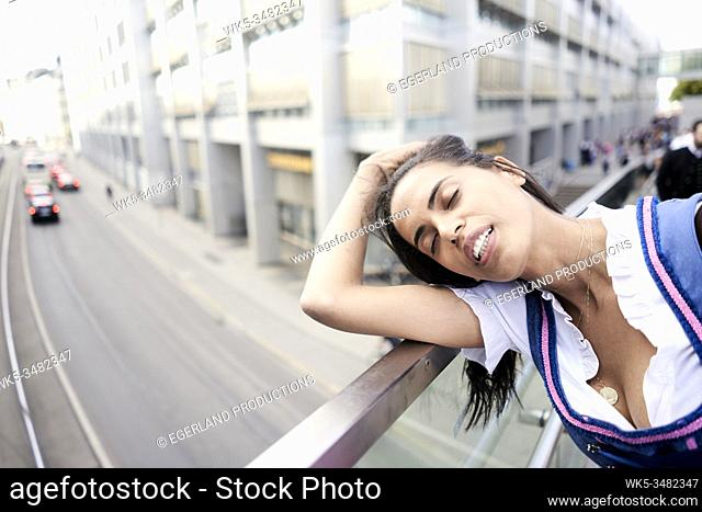 Brazilian woman wearing Dirndl, leaning on railing, exhausted. Munich, Germany
