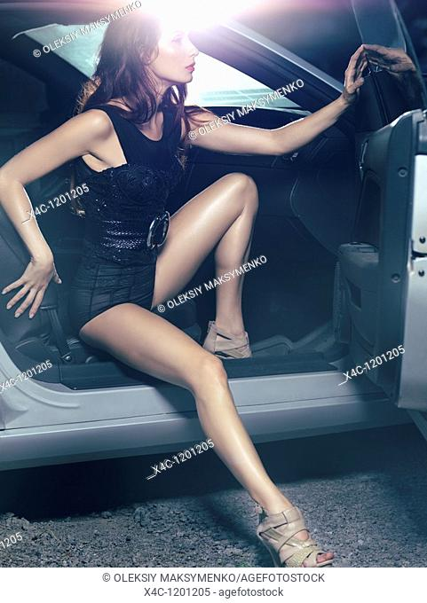 Sexy young woman with beautiful long legs getting out of a luxury car  High fashion photo