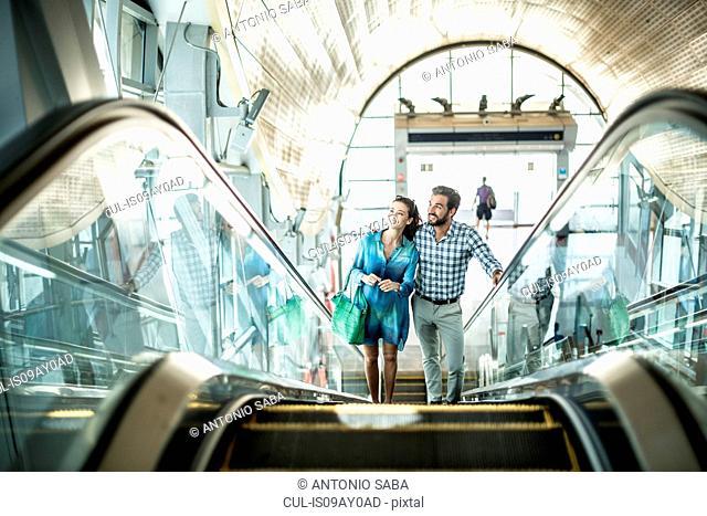 Tourist couple moving up escalator in shopping mall, Dubai, United Arab Emirates