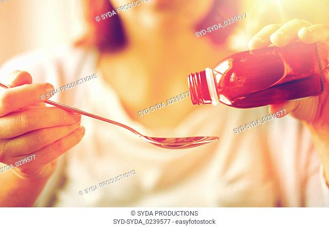 woman pouring medication from bottle to spoon