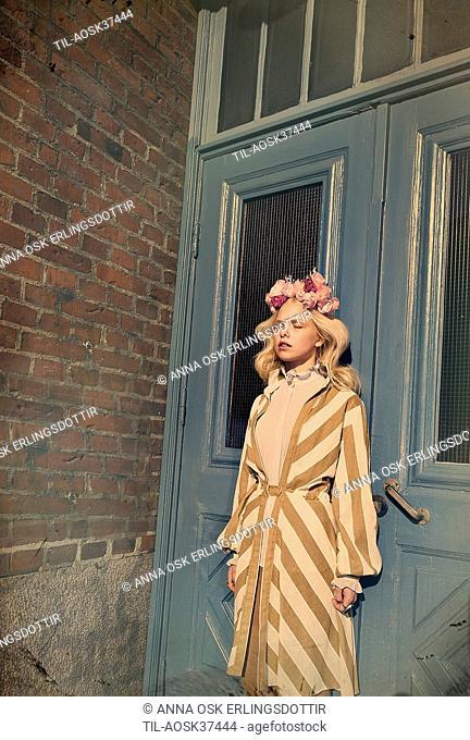 Lone female figure with blonde hair standing by doorway