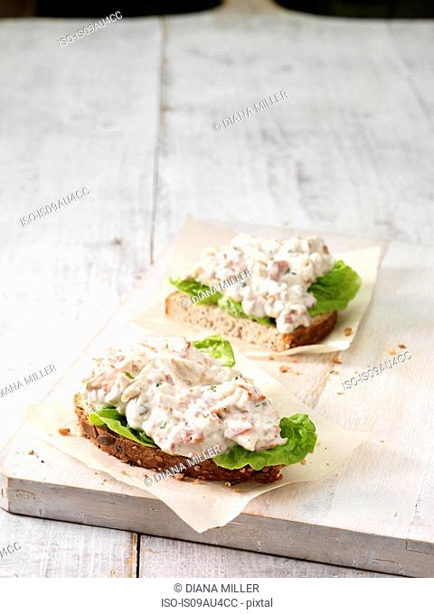High angle view of chicken, bacon and salad leaves on wholemeal bread