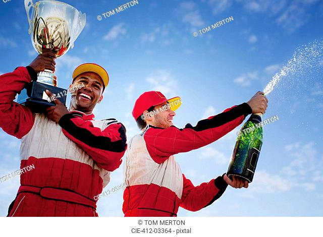 Racers holding trophy and champagne