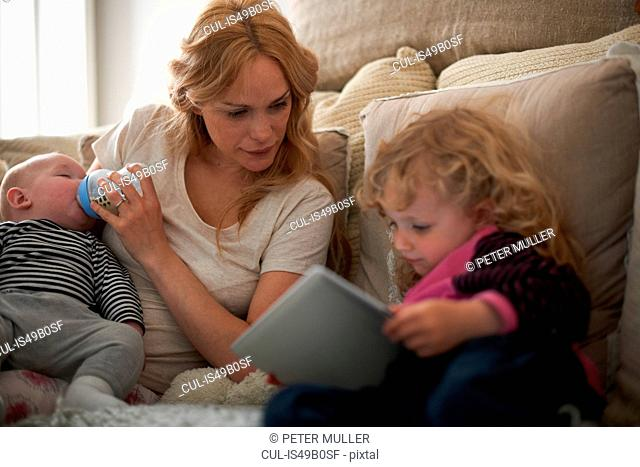 Mother feeding baby son and helping daughter with digital tablet