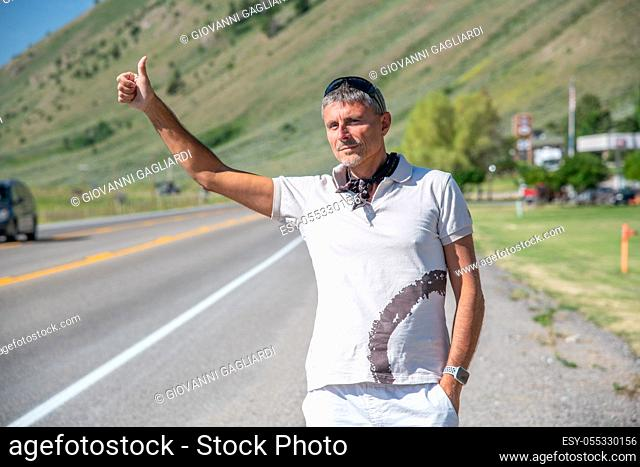 Outdoor shot of travel man hitchhiking along a countryside road in casual t-shirt. Travelling, tourism and holiday concept