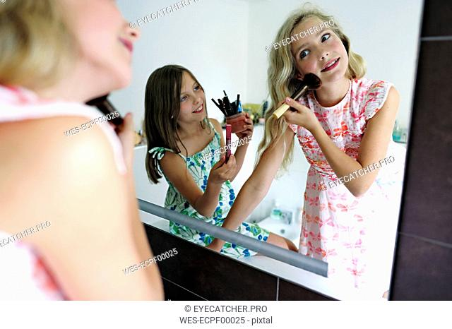 Two girls applying make up in bathroom