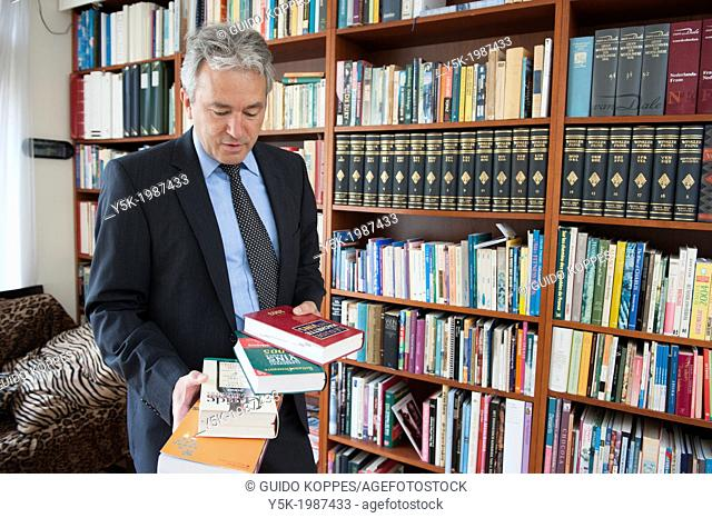 Breda, Netherlands. Wine broker reading books and references in his library at home