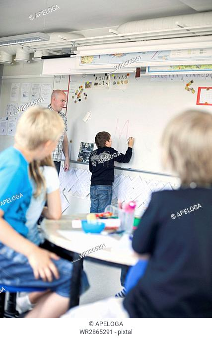 Teacher looking at boy writing on whiteboard in classroom