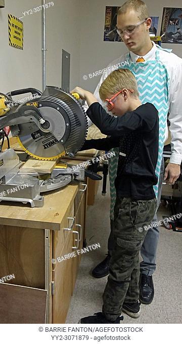 Teacher Assisting 8th Grade Boy with Circular Saw, Wellsville, New York, USA