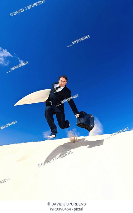 A businessman running to the beach to surf