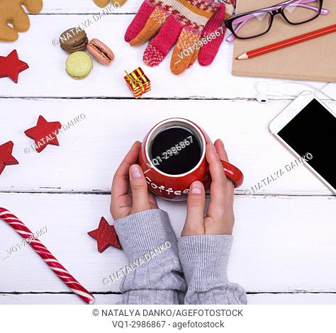 hot black coffee in a red mug in female hands on a white wooden table, top view