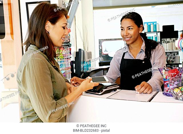 Customer paying in hair salon with cell phone