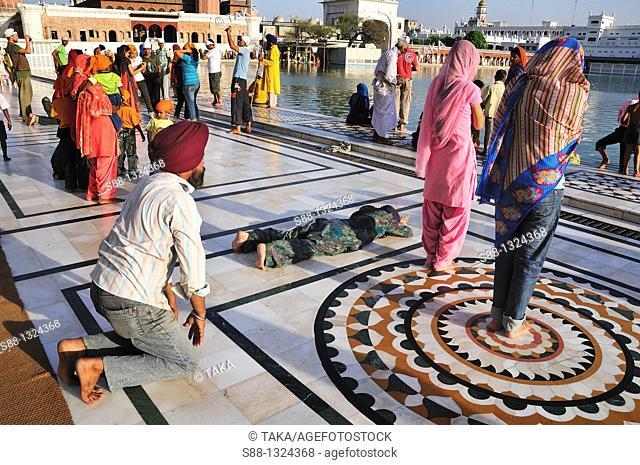 Sikh pilgrims praying for the God in Golden Temple