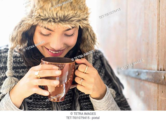 Portrait of smiling young woman drinking from mug