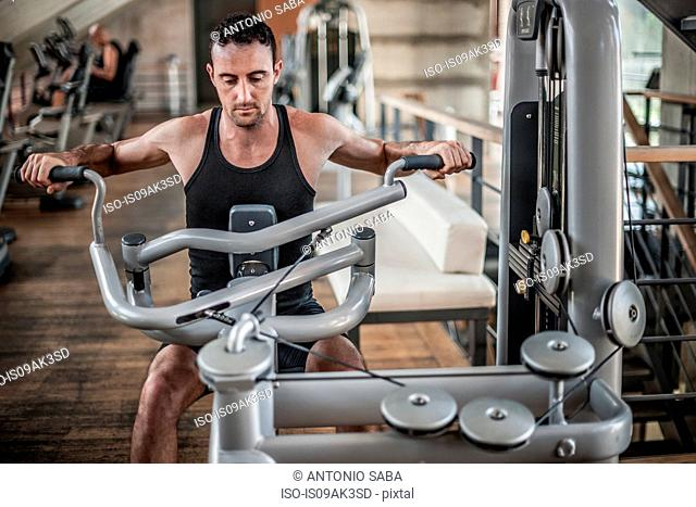 Mid adult man using weight equipment