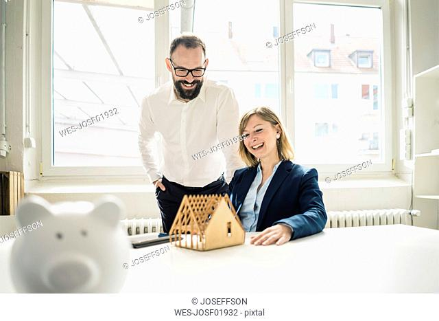 Laughing woman and man with house model and piggy bank in office