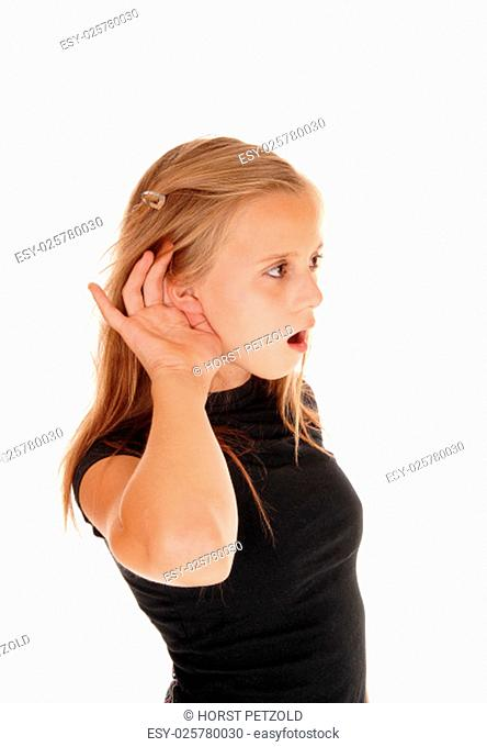 A blond young girl in a black top with one hand behind her ear can not.hear well, isolated for white background.