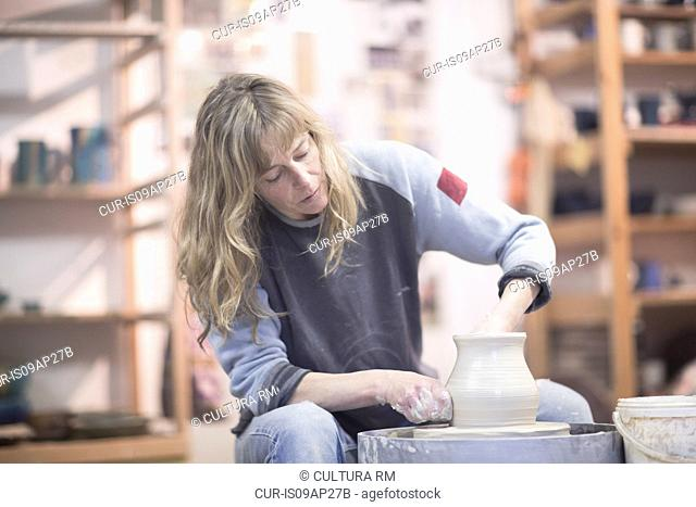 Female potter forming clay pot on pottery wheel in workshop