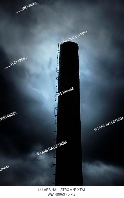 Dark and ominous sky and silhouette of factory chimney. Heavy clouds and darkness. Moody and scary setting in industrial area