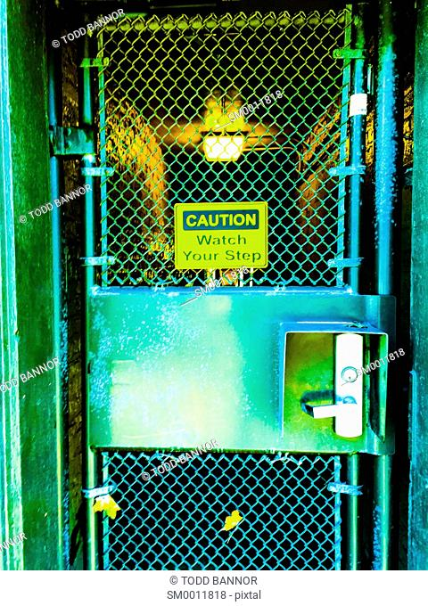 Chain link gate with 'Watch your step' sign