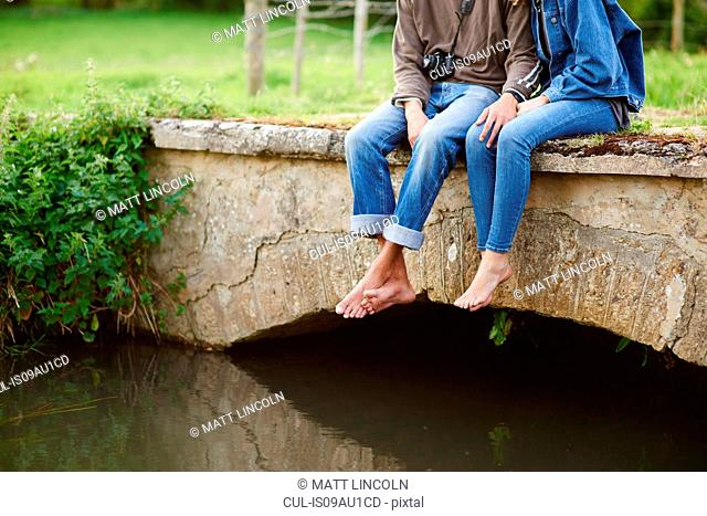 Neck down view of young couple sitting on river footbridge