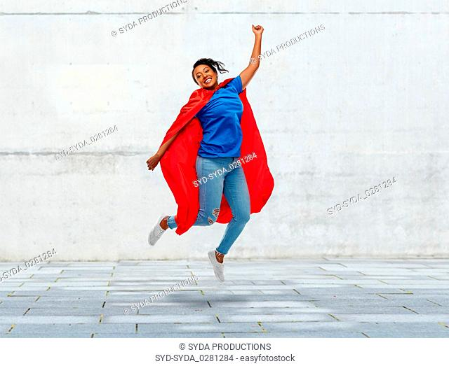 happy african american woman in superhero red cape